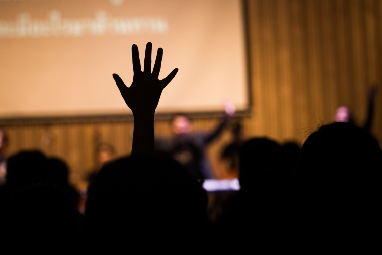 one hand is raised above heads of business people at a conference