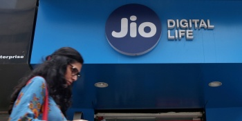 A woman checks her mobile phone as she walks past a mobile store of Reliance Industries' Jio telecoms unit, in Mumbai, India