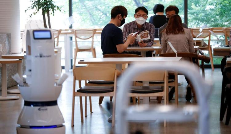 Customers wait at a cafe where a robot that takes orders, makes coffee and brings the drinks straight to customers is being used in Daejeon, South Korea, May 25, 2020.