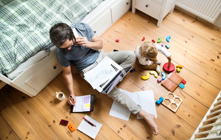 Father working from bedroom floor with his child playing nearby