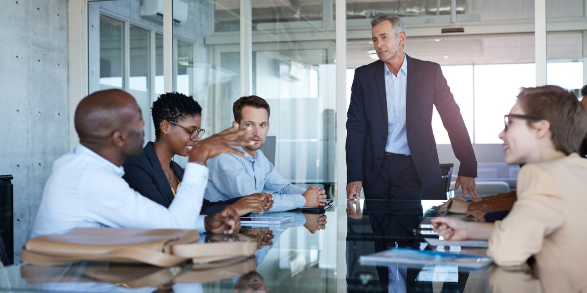 Business people dressed casual/corporate, talking together in large glass conference room
