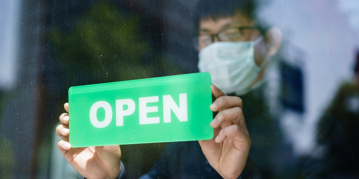 Business owner hangs open sign on door while wearing protective mask