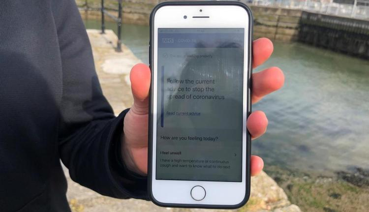 UK National Health Service employee Anni Adams shows a smartphone displaying the new NHS app to trace contacts with people potentially infected with the coronavirus disease (COVID-19) being trialled on Isle of Wight, Britain, May 5, 2020