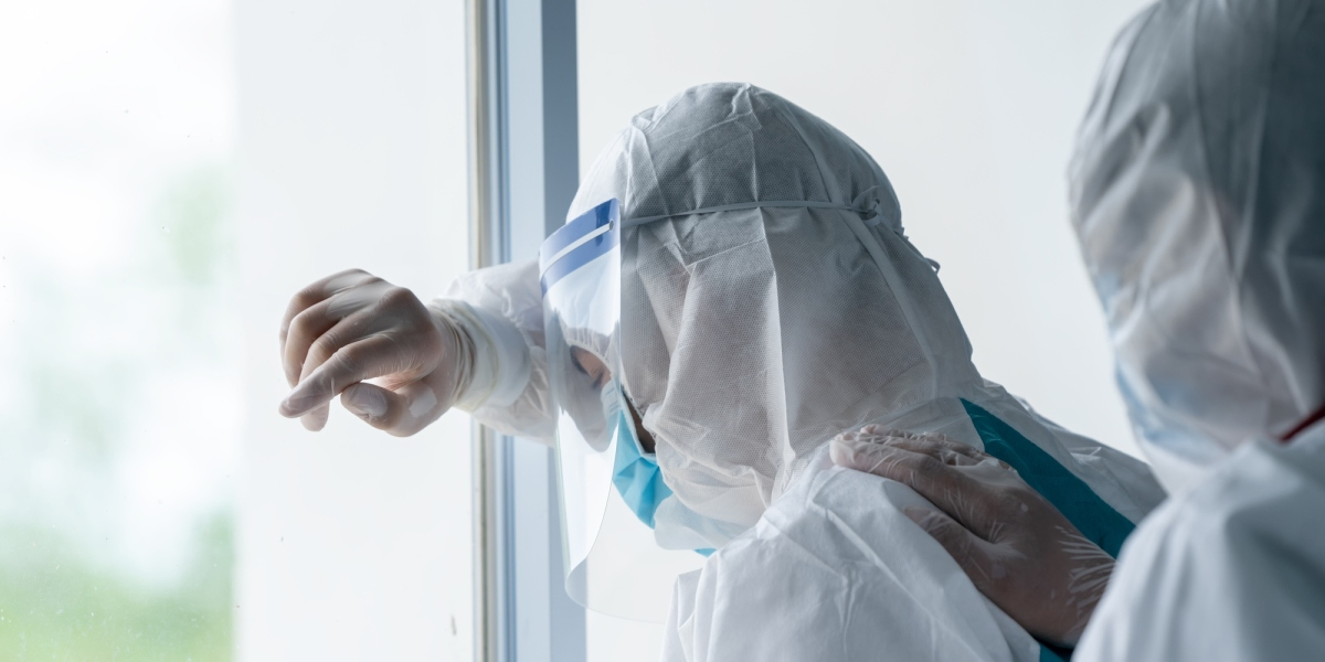 Exhausted doctor wearing protective suit to fight COVID-19