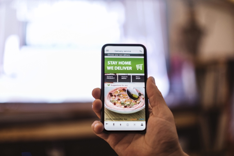 Person holding phone, showing food-ordering app