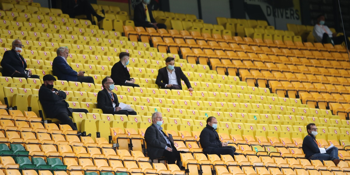 NORWICH, ENGLAND - JULY 11: People look on from the stands whilst social distancing during the Premier League match between Norwich City and West Ham United at Carrow Road on July 11, 2020 in Norwich, England. Football Stadiums around Europe remain empty due to the Coronavirus Pandemic as Government social distancing laws prohibit fans inside venues resulting in all fixtures being played behind closed doors. (Photo by Alex Pantling/Getty Images)