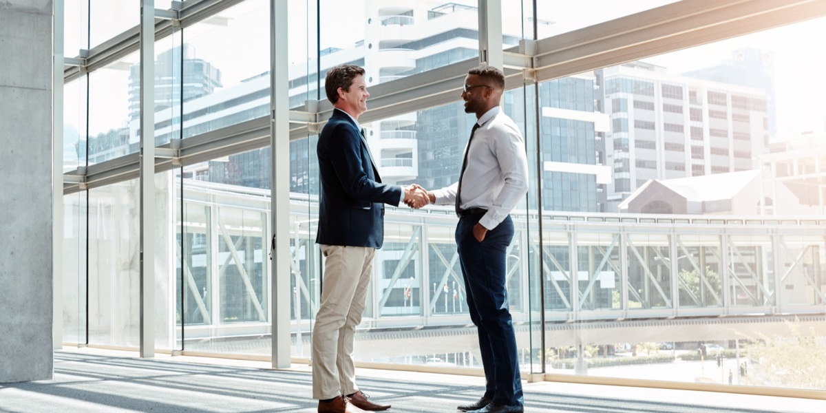 Shot of two businessmen shaking hands in a modern workplace