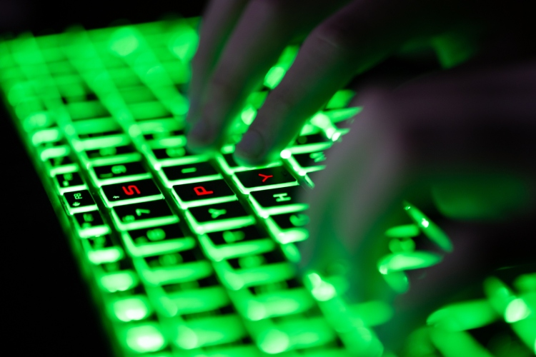 """Digital composite of glowing green keyboard in the dark, the hands of a computer hacker typing and letters """"SPY"""" in red on the keyboard"""