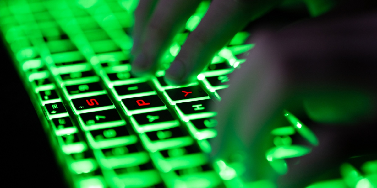 "Digital composite of glowing green keyboard in the dark, the hands of a computer hacker typing and letters ""SPY"" in red on the keyboard"