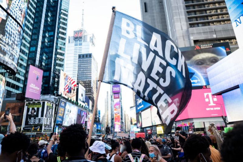 "MANHATTAN, NY - July 26: A protester holds a large flag that says, ""Black Lives Matter"" in Times Square in New York. Many people were wearing masks and observing social distancing due to the coronavirus pandemic. (Photo by Ira L. Black/Corbis via Getty Images)"