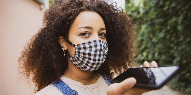 Portrait of a young afro hair woman in the city wearing a cloth protective mask in Italy during Covid-19 coronavirus pandemic