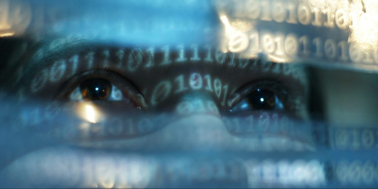 Closeup view of womans face lit by binary code