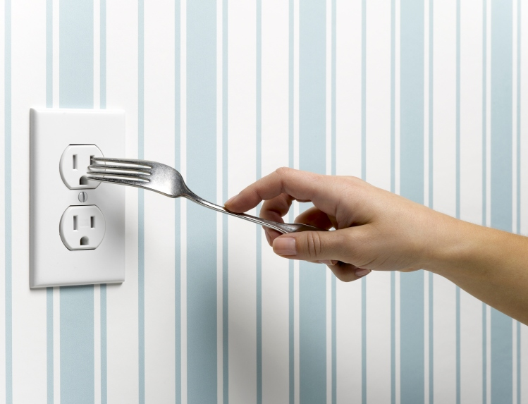 Someone sticking a fork into an electrical socket