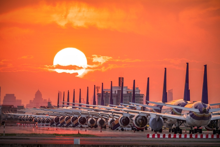 Airplanes grounded due to COVID with orange sky at sunrise
