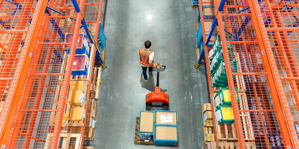 High angle view of warehouse worker pulling a pallet truck at distribution warehouse.