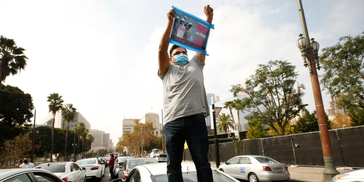 """Rideshare driver Jesus Ibarra stands on his car in support as gig workers held a driving demonstration urging voters to vote """"no"""" on Proposition 22."""