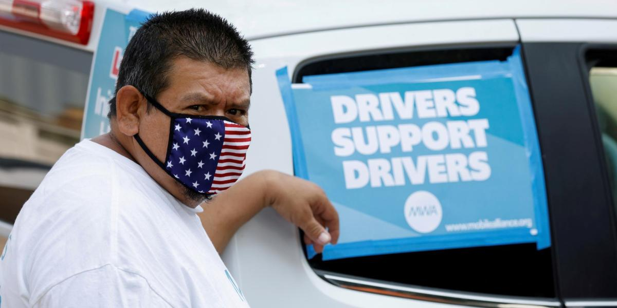 """Rideshare driver Jesus Jacobo Zepeda of Lancaster, California takes part in a rally as part of a statewide day of action to demand that ride-hailing companies Uber and Lyft follow California law and grant drivers """"basic employee rights'', in Los Angeles, California, August 20, 2020."""