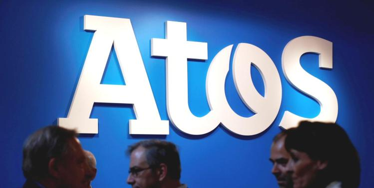 People walk in front of Atos company's logo during a presentation of the new Bull sequana supercomputer in Paris, France, April 12, 2016.