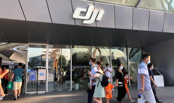 People wearing face masks walk past DJI's flagship store in Shenzhen, Guangdong province, China August 8, 2020.