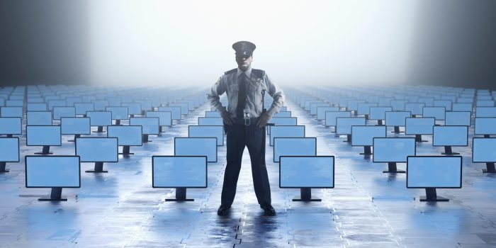 A security guard stands at the front of a roomfull of screens