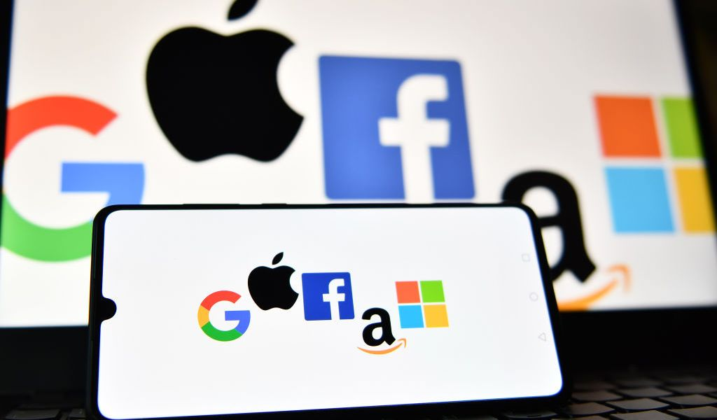 An illustration picture taken in London on December 18, 2020 shows the logos of Google, Apple, Facebook, Amazon and Microsoft displayed on a mobile phone and a laptop screen. (Photo by JUSTIN TALLIS / AFP) (Photo by JUSTIN TALLIS/AFP via Getty Images)