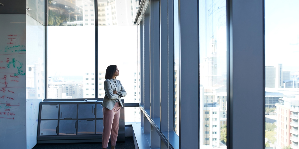Businesswoman standing in corner of big office building and looking out of window