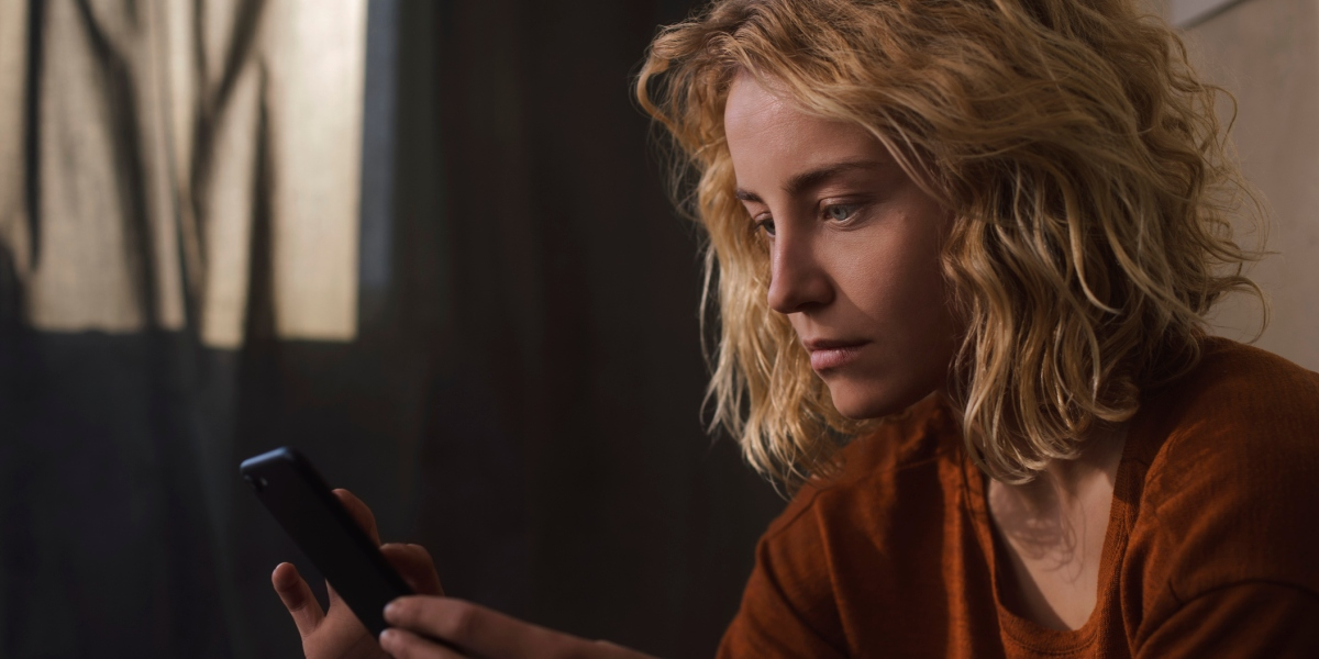 Portrait of blond young woman using cell phone