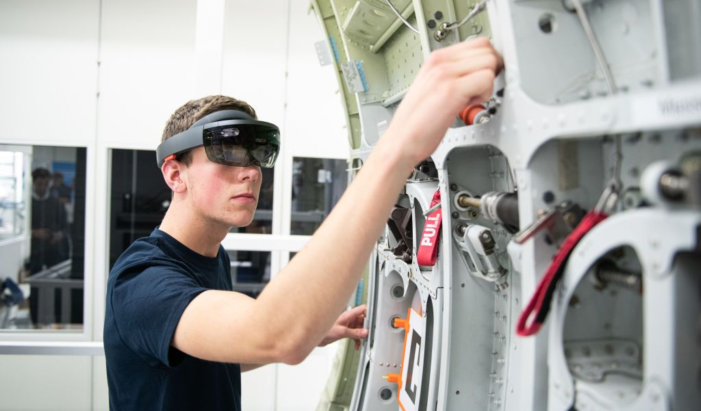 """10 July 2019, Hamburg: During a demonstration, an Airbus trainee shows the use of data goggles (Microsoft Hololens) on an aircraft component. The spectacles work with the """"Mira Mixed Reality"""" application developed by Airbus and are used, among other things, in maintenance and installation. At an event on the Airbus premises, the Hamburg Chamber of Commerce presented a position paper on digital education. Photo: Daniel Reinhardt/dpa (Photo by Daniel Reinhardt/picture alliance via Getty Images)"""
