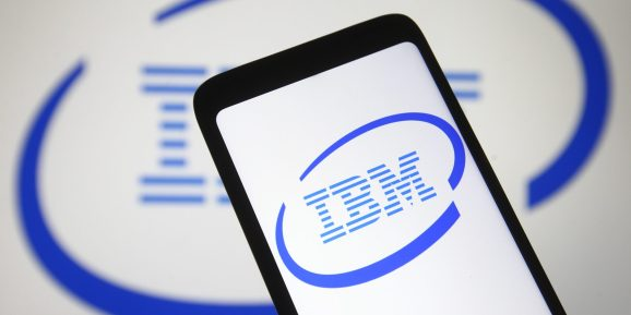 IBM logo is seen on a smartphone and a pc screen.