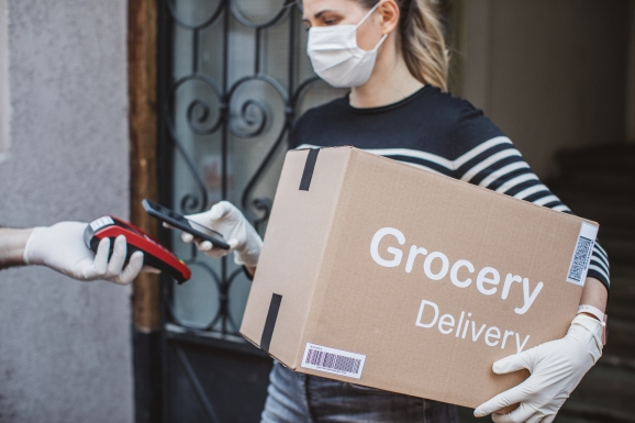 Delivering food ordered online while in home isolation. Women taking over package and paying