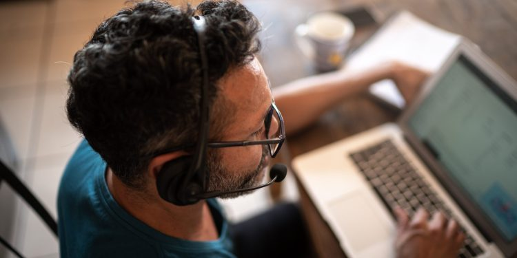 Person working from home or is on a customer call with a headset and laptop