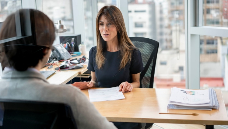 HR manager at her office talking to employee cheerfully while holding some paperwork