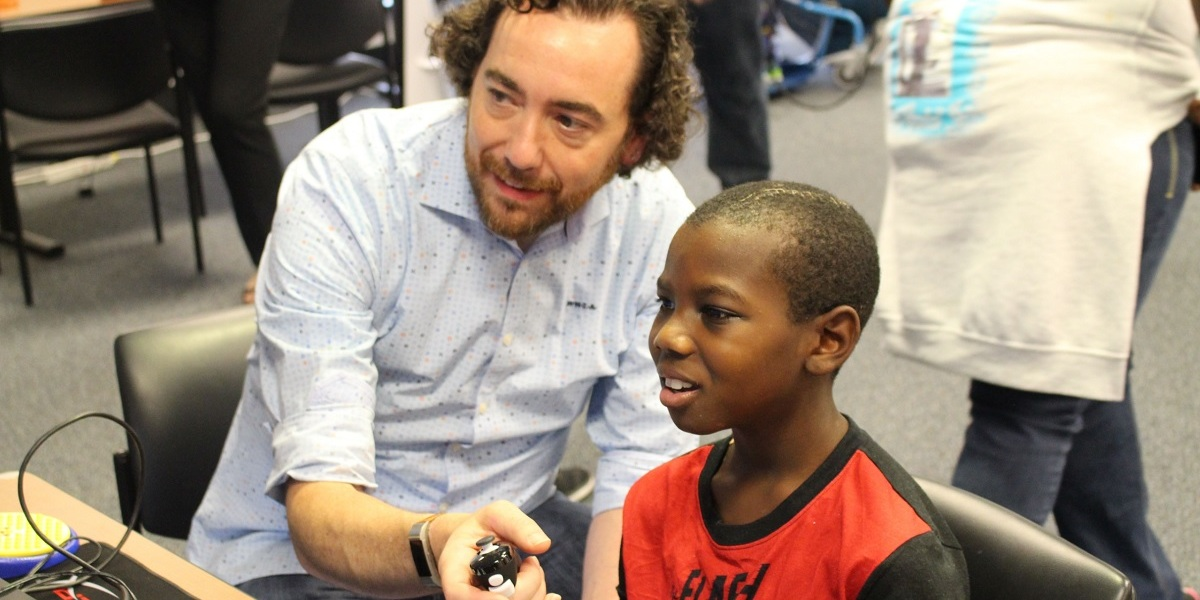 Mark Barlet of AbleGamers shows a child how to play video games using an inclusive controller.