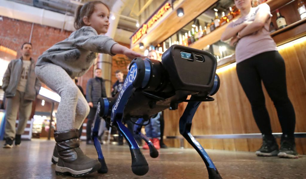 MOSCOW, RUSSIA - MARCH 14, 2021: A child approaches an A1 robot dog by Unitree Robotics during a presentation event at Depo Moscow Food Mall. Unitree Robotics is a China-based start-up company that develops and manufactures quadruped robots. Robot dogs are designed to help patrol and explore areas, render maps, and fulfil logistic and research objectives. They can also be kept at home as ordinary pets. Valery Sharifulin/TASSEDITORIAL USE ONLY; NO COMMERCIAL USE; NO ADVERTISING (Photo by Valery SharifulinTASS via Getty Images)