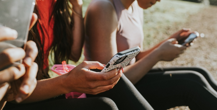 Three woman sit outside in the sun and hold their smart phones. They all look at their screens, while using fingers and thumbs to type. Conceptual with space for copy.