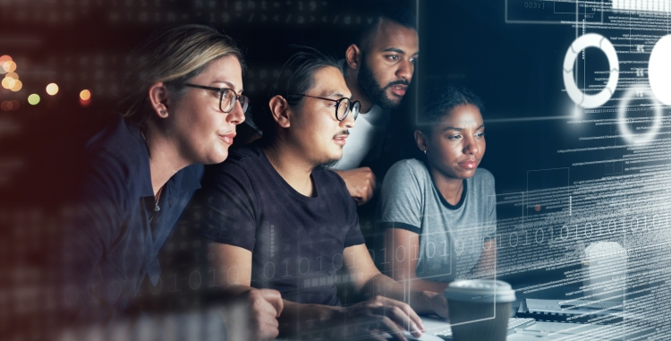 Shot of a group of programmers working together on a computer code at night