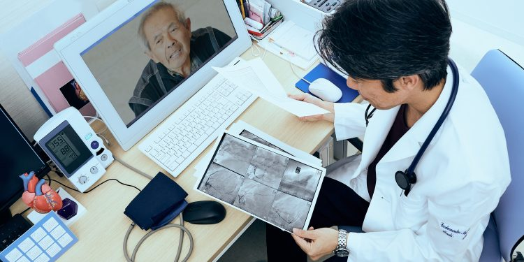 Cardiovascular doctor looking at coronary x-ray output during telehealth appointment.