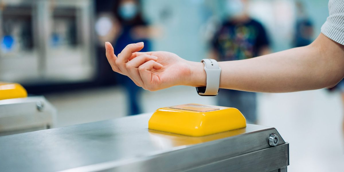 Person checking in at subway station using contactless payment for subway ticket via smartwatch