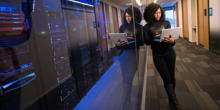 Woman on a laptop next to a server room