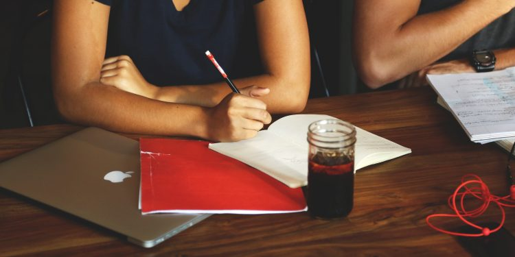 Table in front of a person in a meeting. Person is writing in a notebook, with a laptop, drink, and folder next to them.