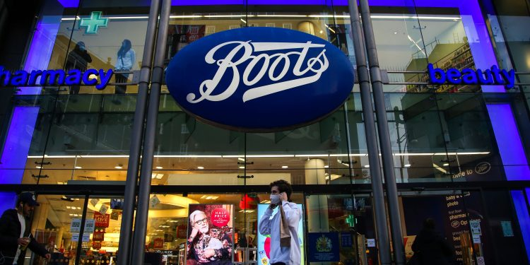 A man wearing a face mask walks past a branch of Boots on