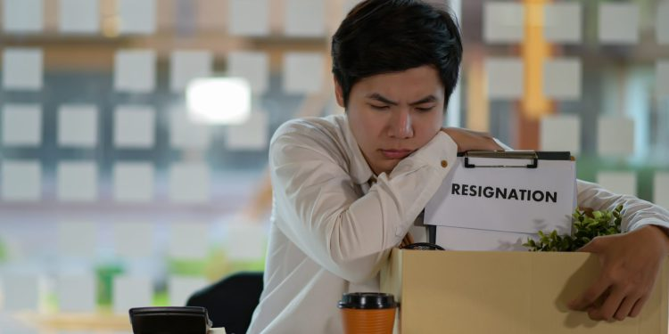 """Upset person with a box. Sign on the box says """"Resignation"""""""