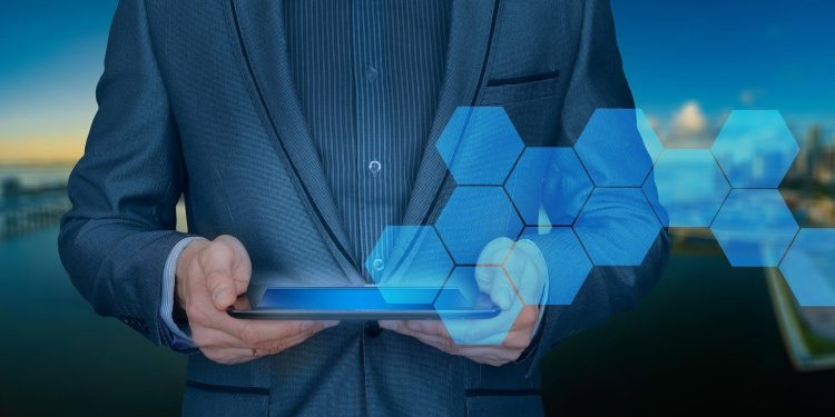 Graphic of a businessperson holding a tablet with hexagons coming out of it. A city in the background.