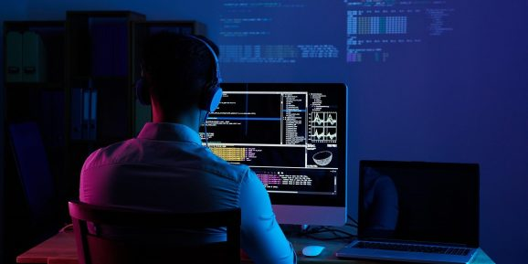 Software developer writing code on a desktop computer with a laptop next to it. Code is also projected on the wall. Developer appears to be working from home at a desk wearing headphones