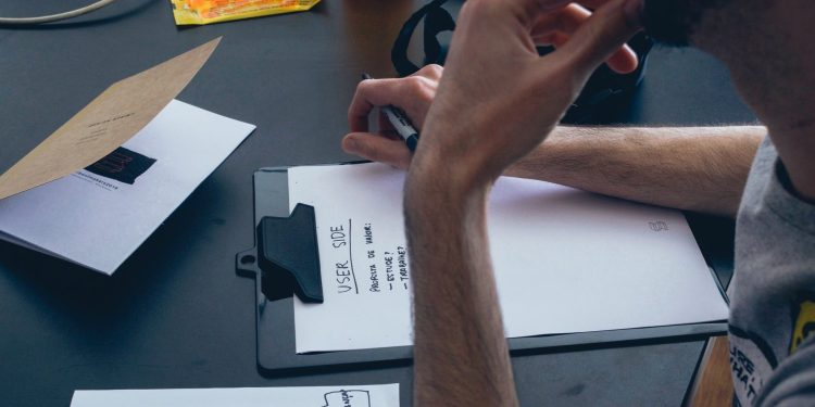 A person writing on a clipboard paper. The paper is about user experience