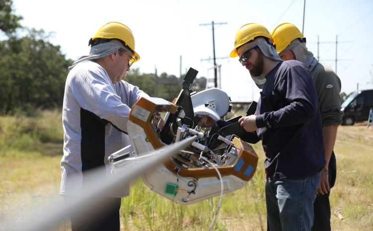 Technicians attach Facebook's Bombyx robot to a telephone wire.